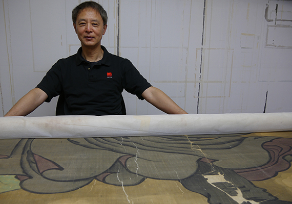Jing Gao standing in front of painting laid down on table
