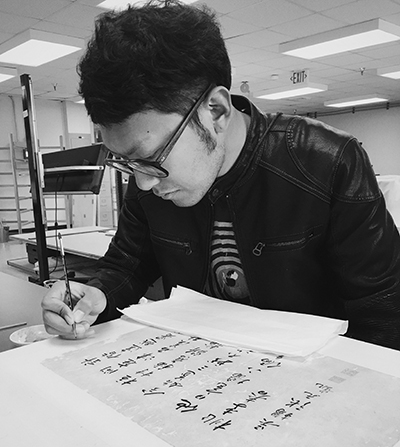 Zhichao Lyu working with a brush on a Chinese scroll