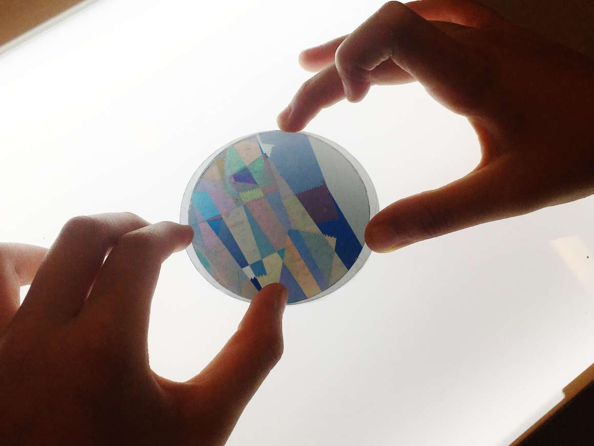 child holding Petri dish with polarizing film over a light box