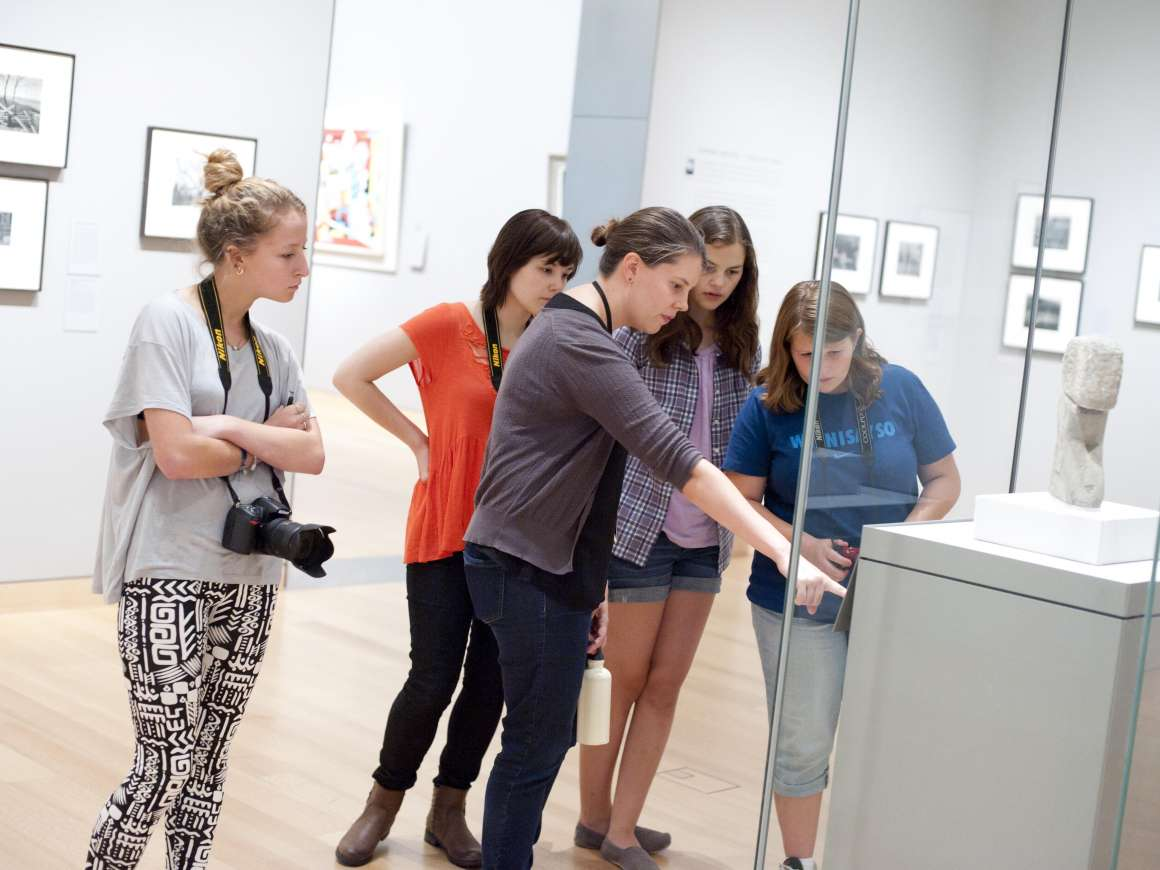 Teens looking at label for sculpture in display case
