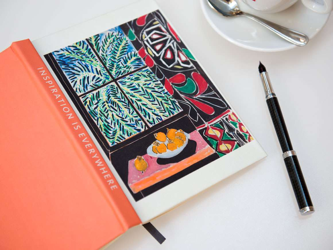 Open hardcover journal with Henri Matisse's painting, Interior with Egyptian Curtain, on cover, placed next to teacup and pen on table