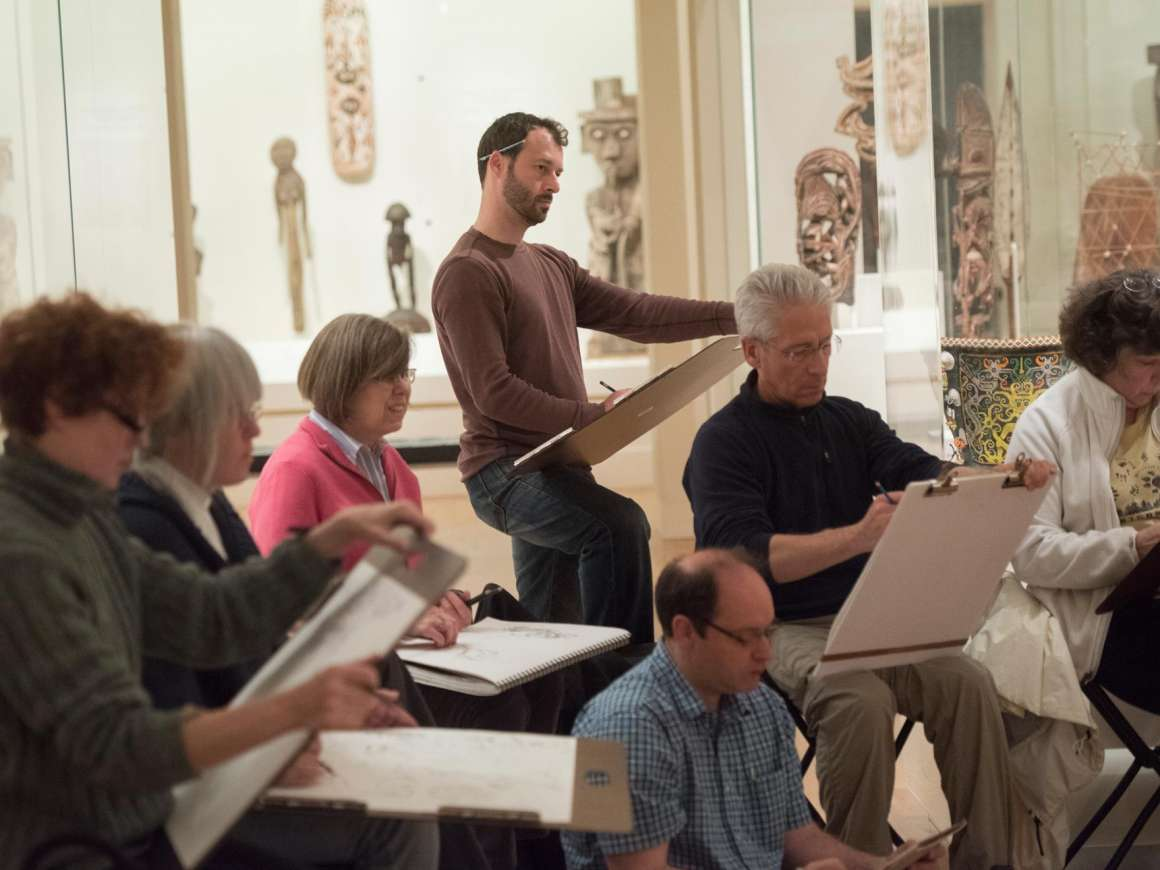 Man drawing on sketchpad amongst seated artists in gallery