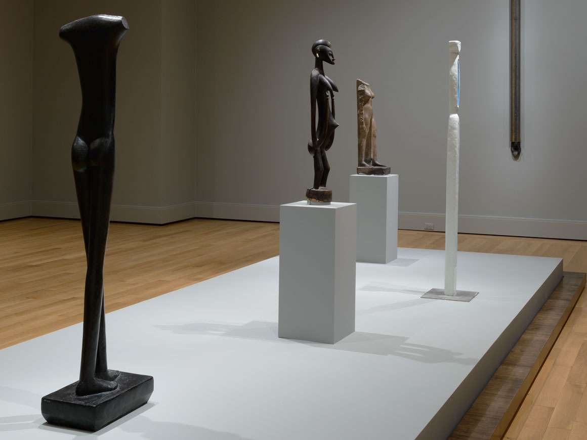 Tall sculptures displayed on central platform in Gallery 155