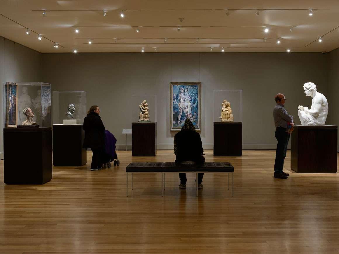 Visitors looking at various sculptures in Gallery 155