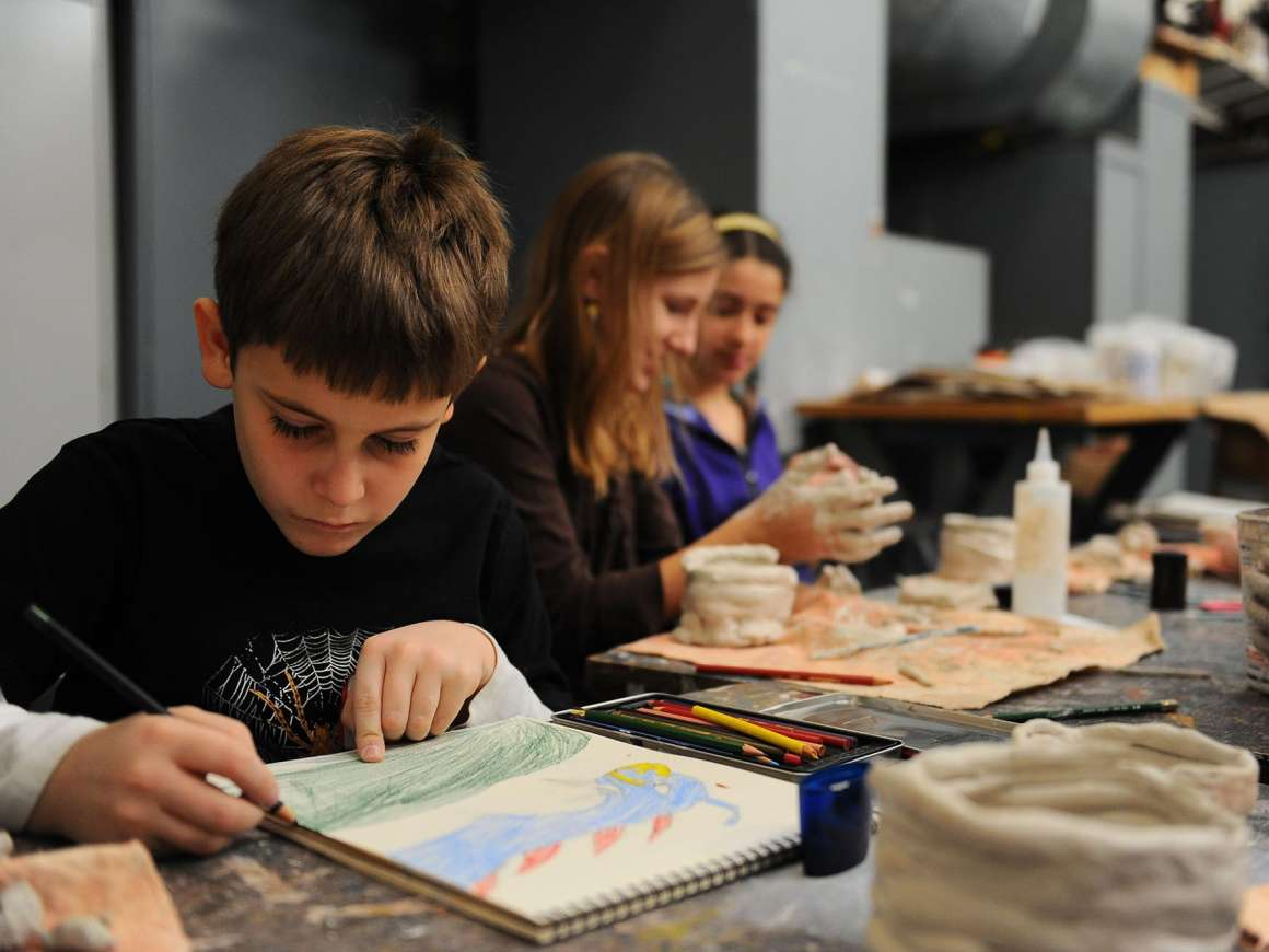 Youth drawing with colored pencils in foreground; others modeling with clay in background