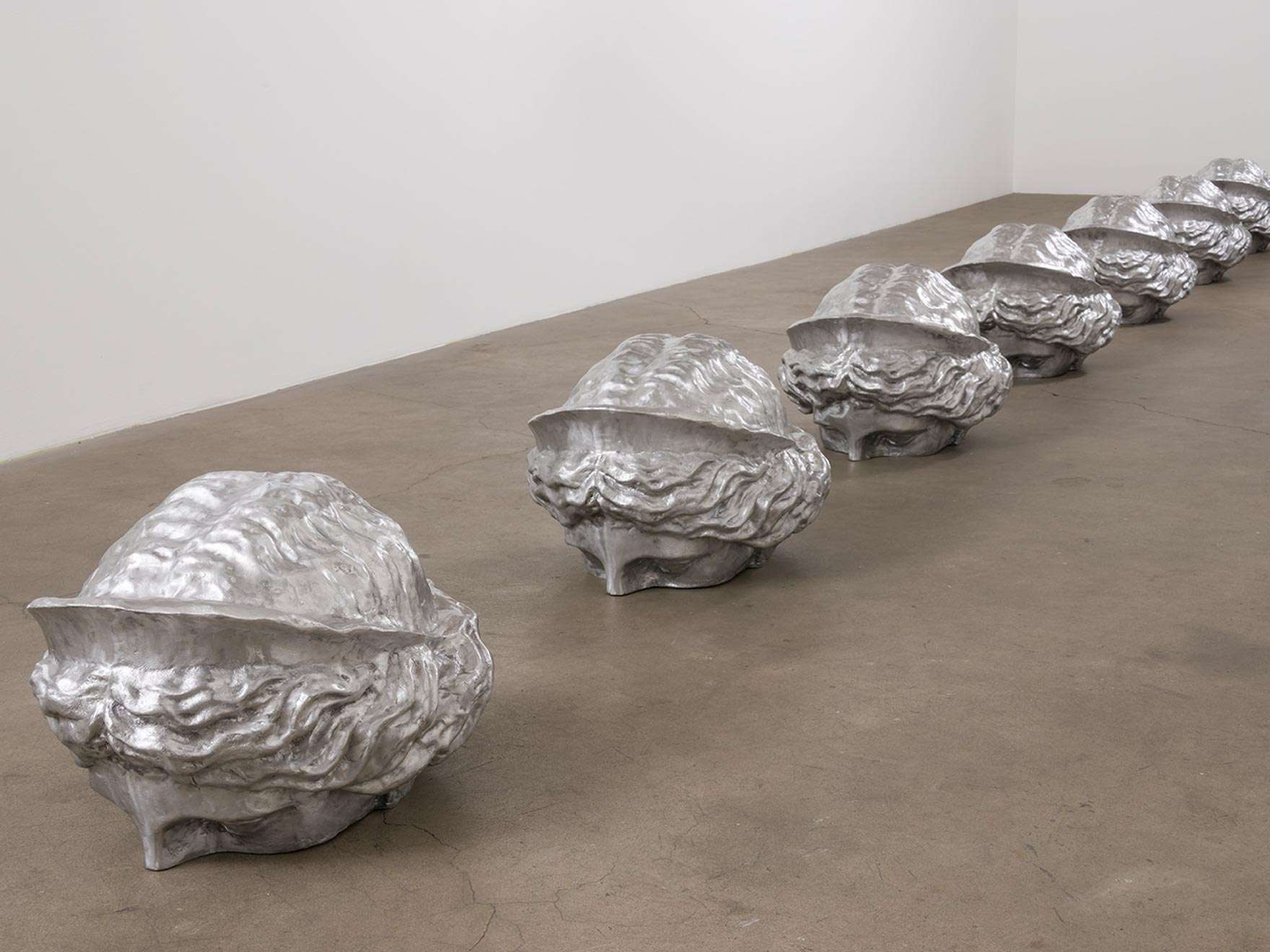 A row of seven polished cast aluminum heads of Juno