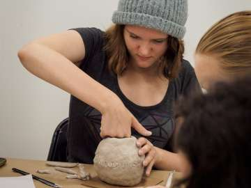 Teen sculpting with clay