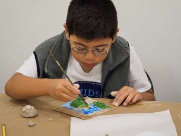 boy painting clay tile