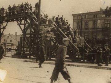 """Henryk Ross, Lodz Ghetto: Boy walking in front of the bridge crossing Zigerska (the """"Aryan"""") street, 1940-44"""