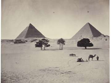 The Giza pyramids of Khufu and Khafra, the pyramid of Khenetkawes, and the head of the Great Sphinx with trees and camels in foreground, looking northwest