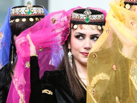 Close-up of dancers in ornate headresses with brightly colored veils