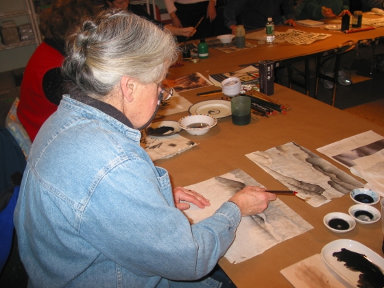 Woman sitting at table working on Chinese brush painting and calligraphy