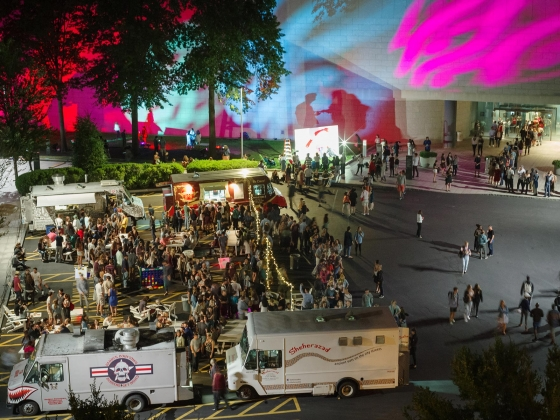 Crowds and food trucks outside Linde Family Wing at night