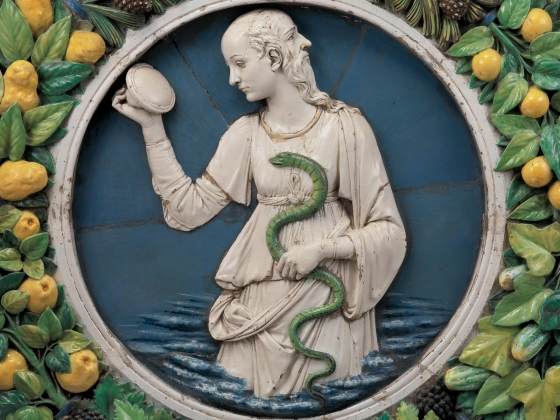 Glazed terracotta sculpture by Andrea della Robbia, featuring two-faced person in the center holding a snake and mirror