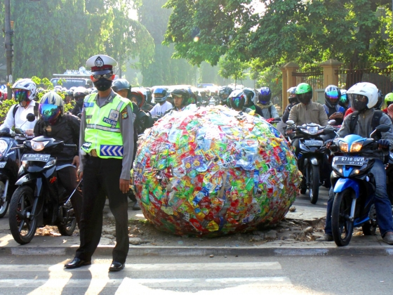 Big ball of snack wrappers on sidewalk, surrounded by riders on motorbikes