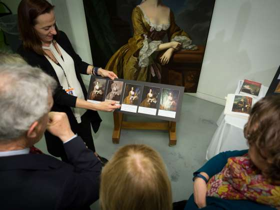 Patrons looking at x-ray images of conservation treatments on textile objects