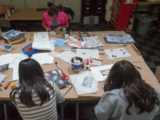Three teens work on printmaking in February vacation week design class