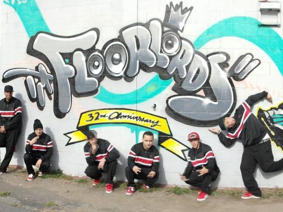 Floorlords dancers posing in front of graffiti logo