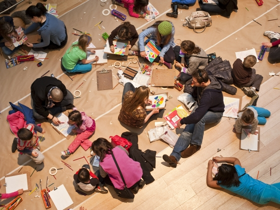 Children and adults sitting on gallery floor coloring