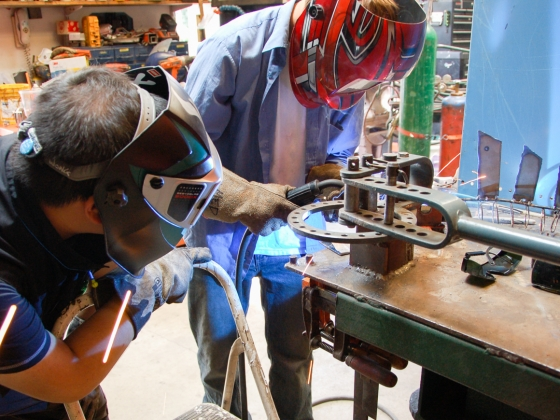 Pair of students work on welding project at workbench
