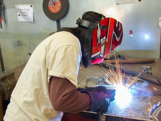 Woman leans over welding with red safety mask