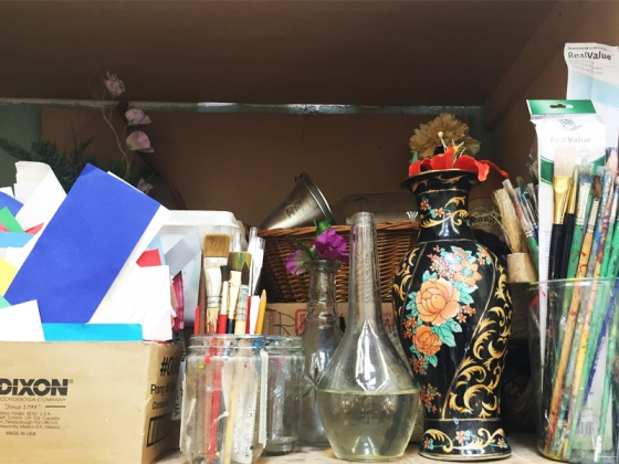 Shot of paper, brushes, glass bottles and supplies in supply closet