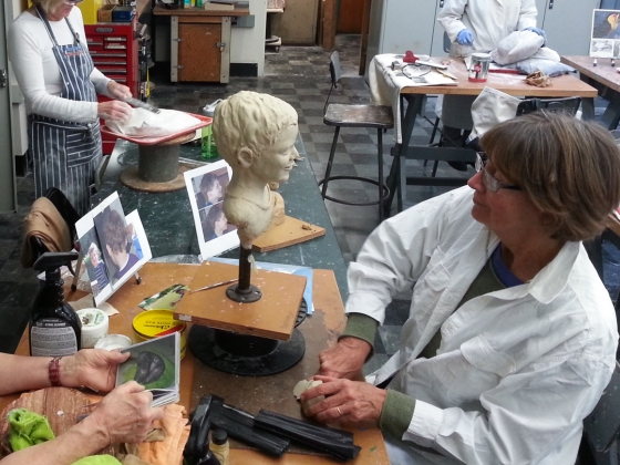 Woman sculpts clay bust of child in sculpture class