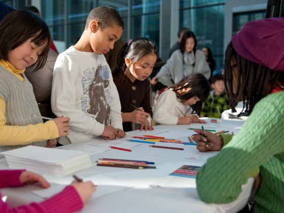 Kids standing around table drawing with colored pencils on white cards