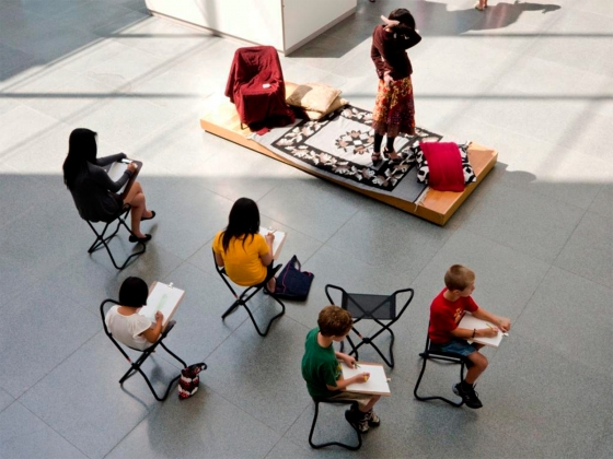 Visitors sitting on foldable chairs in Shapiro Family courtyard sketching model standing on small platform with rug and chair