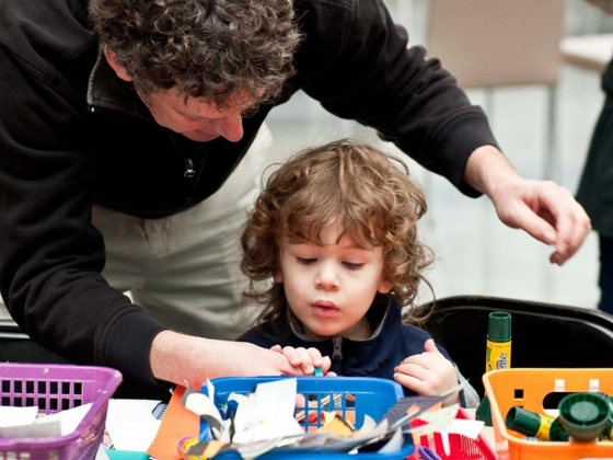 Adult helping child with art project at crafts table