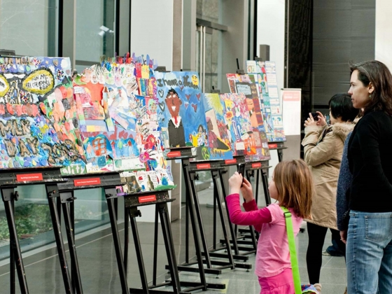 Young visitor holds up smartphone to take a photograph of row of artwork on easels