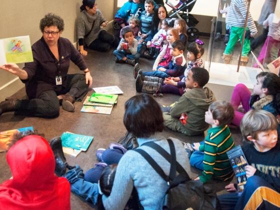 Children sitting on gallery floor around storyteller holding up book