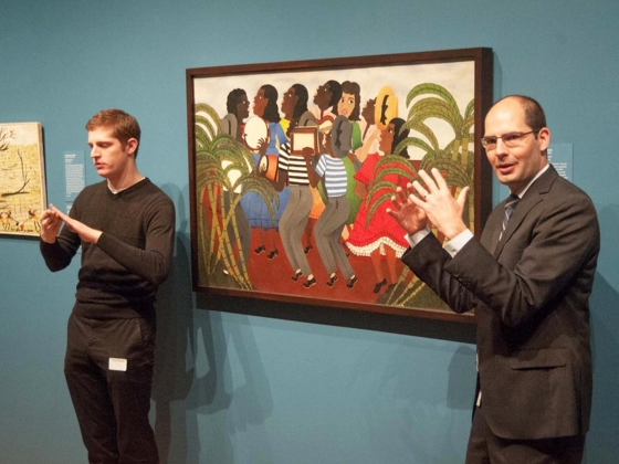 Curator standing next to painting, talking animatedly, with American Sign Language interpreter on opposite side of painting