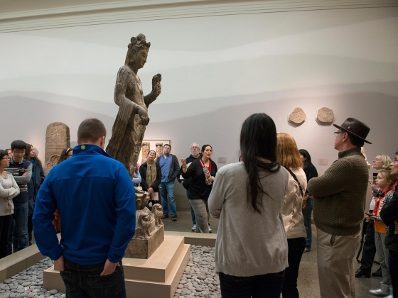 Visitors standing around statue of Guanyin, listening to guide