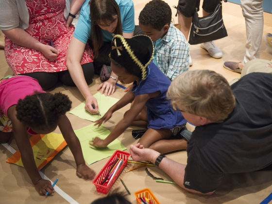Children drawing on colored paper while adults supervise