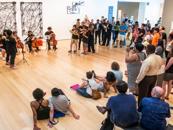 Visitors gathered around listening to musicians performing in gallery