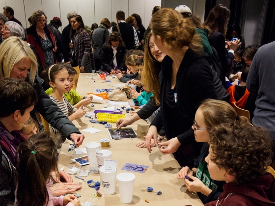 Youths and adults standing at long table making dreidels