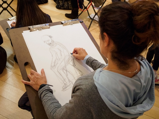 Woman sketching a bearded man sitting on large drawing pad