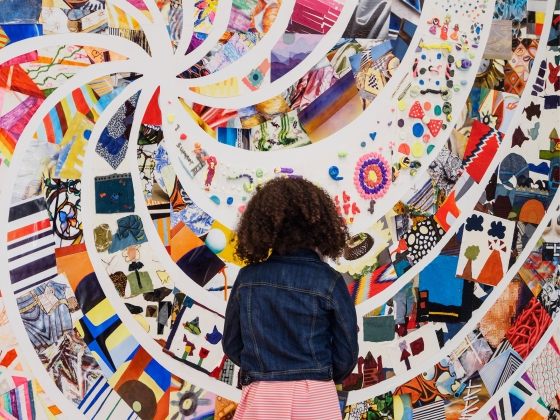 Young visitor looking at spiral of Community Arts Initiative artwork