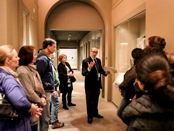 Curator surrounded by visitors talks about Assyrians objects in display cases