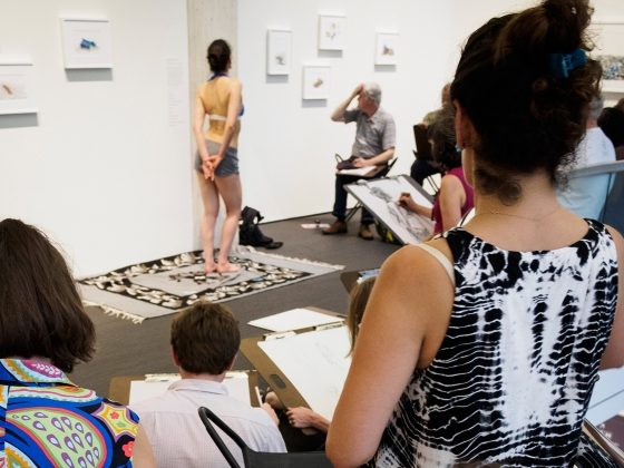 Visitors in crowded gallery draw model standing with arms behind her
