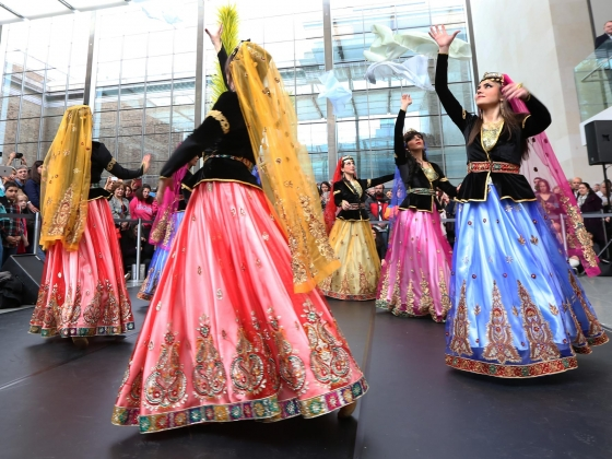 Circle of dancers in colorful dresses and veils perform traditional Persian dance