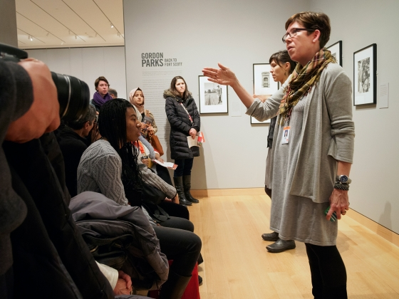 Curator Karen Haas speaks in front of crowd of visitors in Gordon Parks exhibition