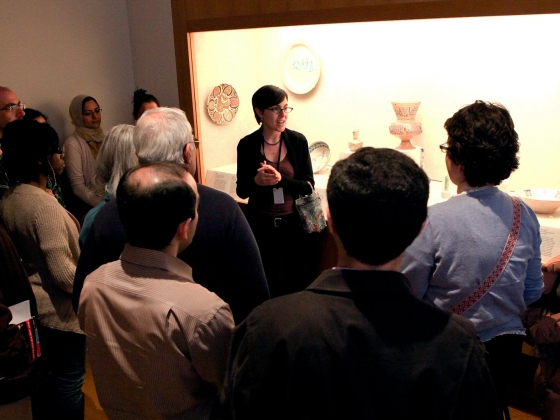 Curator talking to group of visitors in front of display case of Persian ceramics