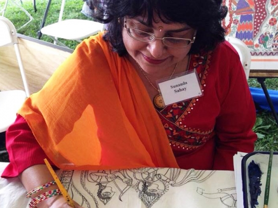 Woman sitting outside at table drawing on paper, demonstrating Madhubani
