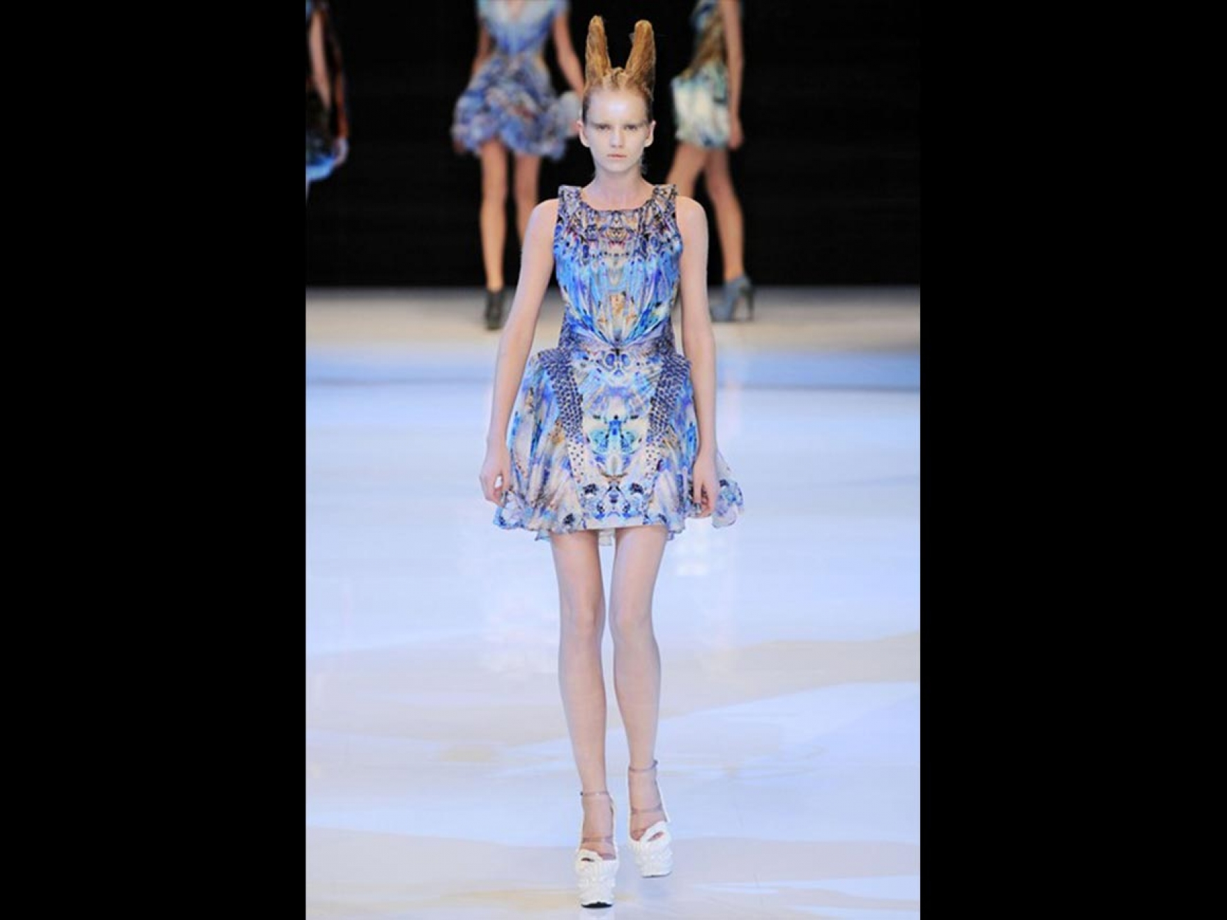 Fashion model wearing blue and white dress on runway