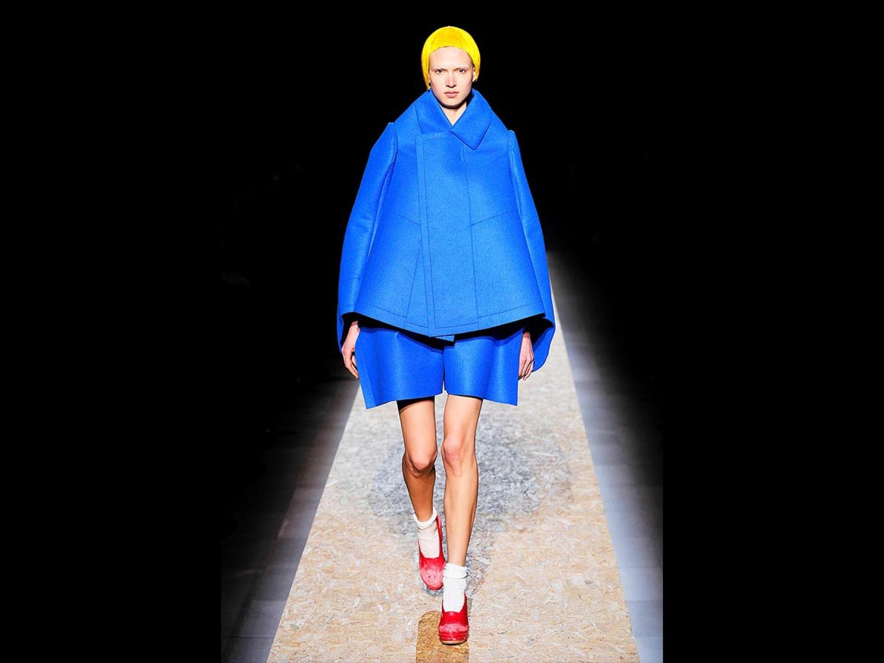 Fashion model wearing large blue jacket and shorts, walking on runway