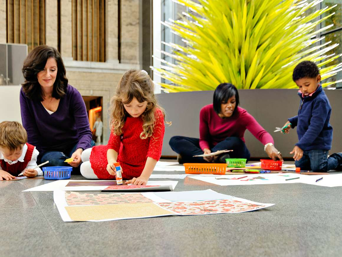 Parents and their kids work on art projects on the floor of the Shapiro Family Courtyard