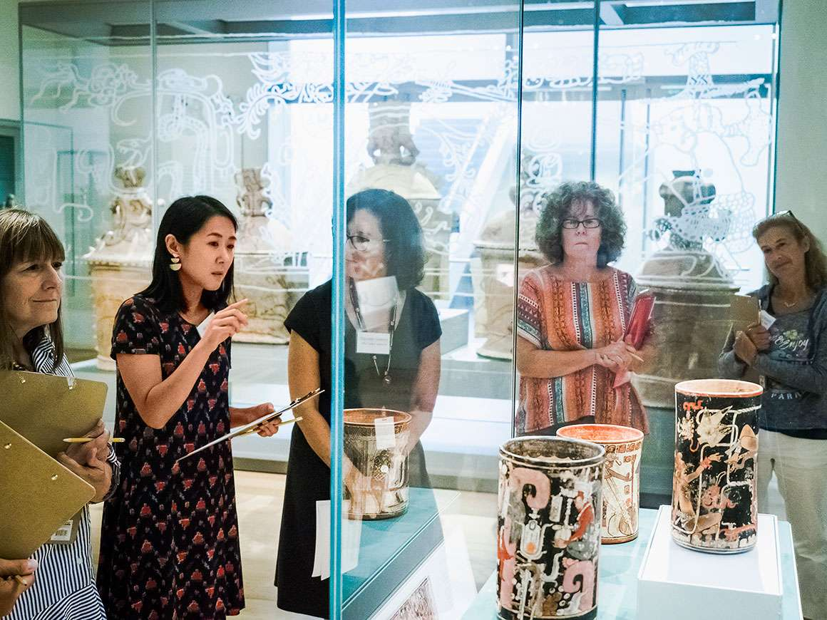 Teachers attending workshop stand around display case featuring Mayan cylinders