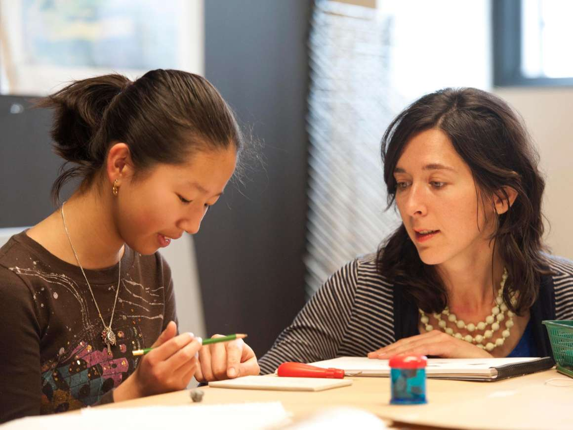 Instructor advising teenage student on drawing